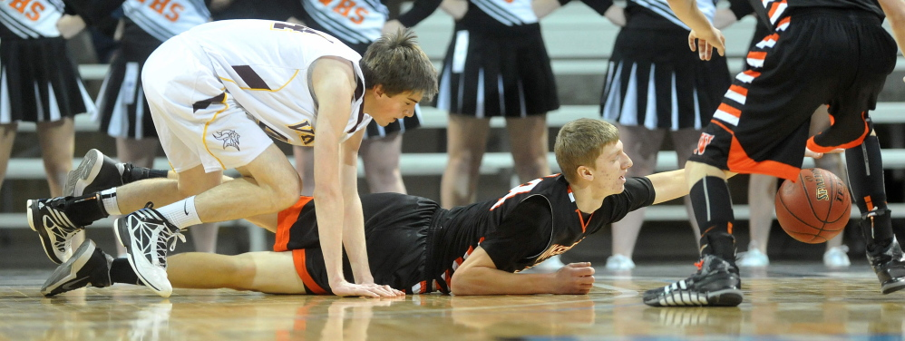 Winslow's Justin Martin dives for a loose ball in front of Caribou's Kameron Manter during an Eastern Class B boys' basketball quarterfinal Saturday at the Cross Insurance Center in Bangor. Caribou won, 63-61.