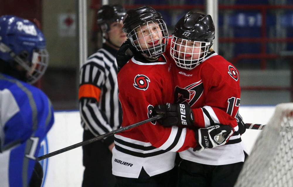 Gabe Souza/Staff Photographer Elizabeth Gross, left, is congratulated by Scarborough teammate Megan Doak after scoring one of her three goals Saturday in the girls' hockey state championship game against Lewiston at the Androscoggin Bank Colisee. Scarborough won, 3-1.