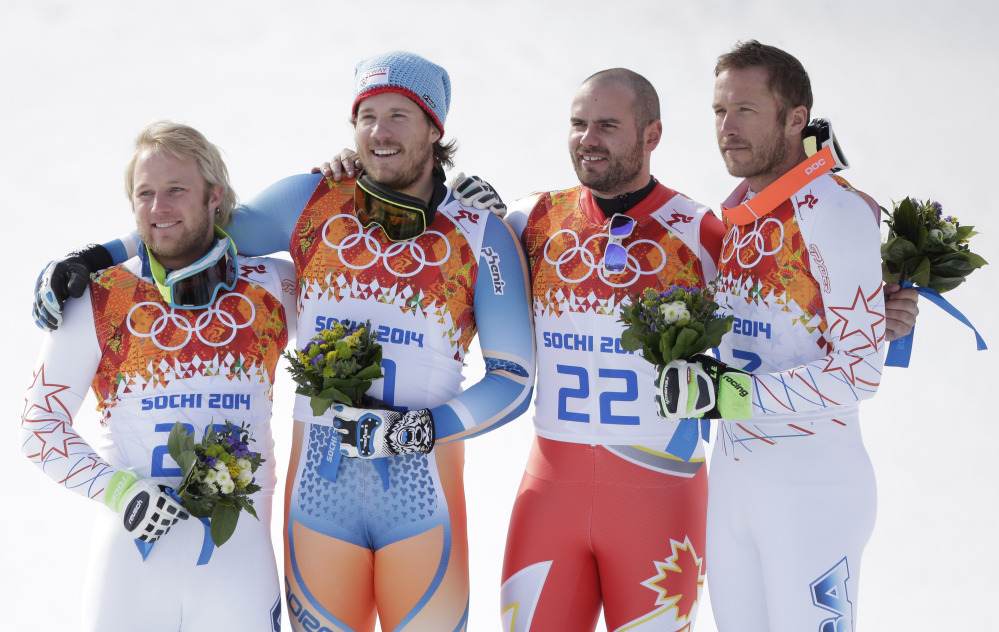 Men's super-G medalists from left, United States' Andrew Weibrecht (silver), Norway's Kjetil Jansrud (gold), Canada's Jan Hudec (bronze) and United States' Bode Miller (bronze) pose for photographers on the podium for a flower ceremony at the Sochi 2014 Winter Olympics.