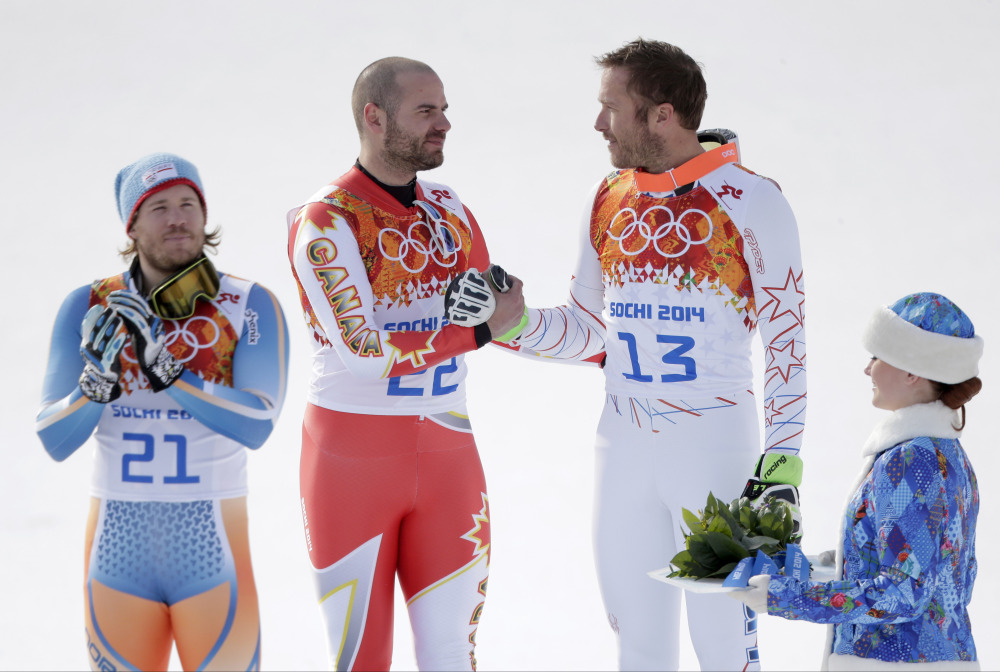 Men's super-G joint bronze medal winners Canada's Jan Hudec and United States' Bode Miller shake hands on the podium as gold medal winner Norway's Kjetil Jansrud stands at left during a flower ceremony at the Sochi 2014 Winter Olympics.