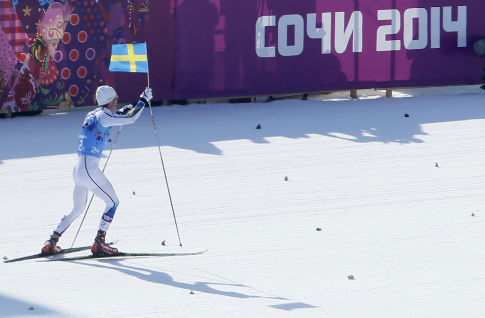Sweden's Marcus Hellner skis with the Swedish flag as his team wins the gold during the men's 4x10K cross-country relay at the 2014 Winter Olympics, Sunday in Krasnaya Polyana, Russia.