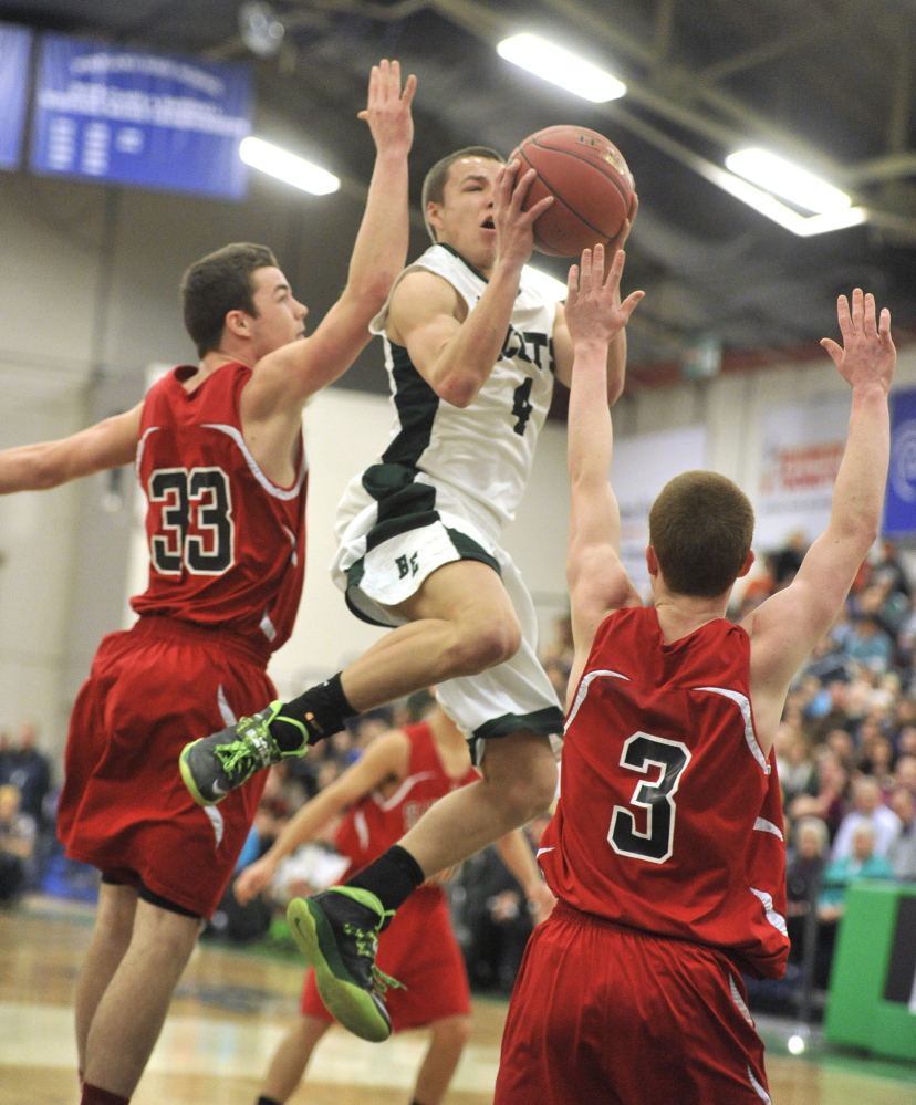 Dustin Cole goes up for a layup against Sanford's Joshua Schroder, left, and Evyn Nolette during Bonny Eagle's 66-49 win Monday morning in a Western Class A boys' basketball quarterfinal at the Portland Expo. Cole scored 33 points to help the Scots advance to the semifinals against Falmouth.