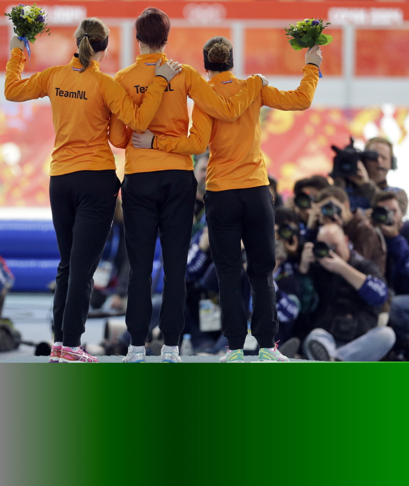 Athletes from the Netherlands, from right to left, silver medalist Ireen Wust, gold medalist Jorien ter Mors and bronze medalist Lotte van Beek celebrate during the flower ceremony for the women's 1,500-meter speedskating race at the Adler Arena Skating Center during the 2014 Winter Olympics in Sochi.