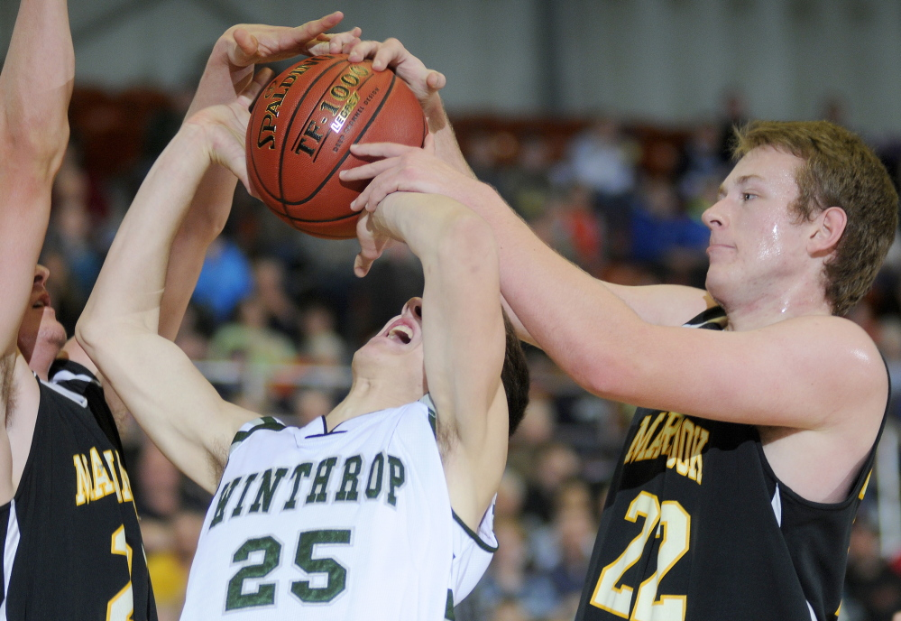 Cam Brochu, left, and Brad Worster of Maranacook block a shot by Dakota Carter of Winthrop during Maranacook's 68-52 win Monday night in a Western Class C boys' basketball quarterfinal at the Augusta Civic Center.