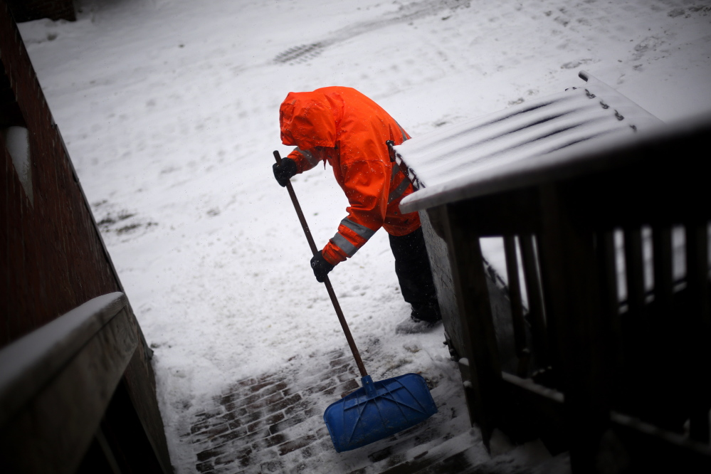 Brandon Dunham of Lawn Enforcement shovels out behind businesses on Fore Street on Thursday. More snow is expected Tuesday.