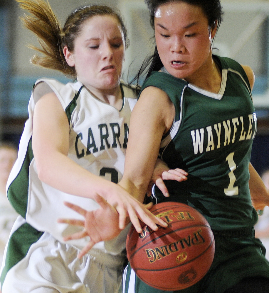 Carrabec's Bailey Atwood, left, and Helen Gray-Bauer of Waynflete battle for the ball during their Western Class C quarterfinal Tuesday at the Augusta Civic Center. Carrabec won, 49-37.