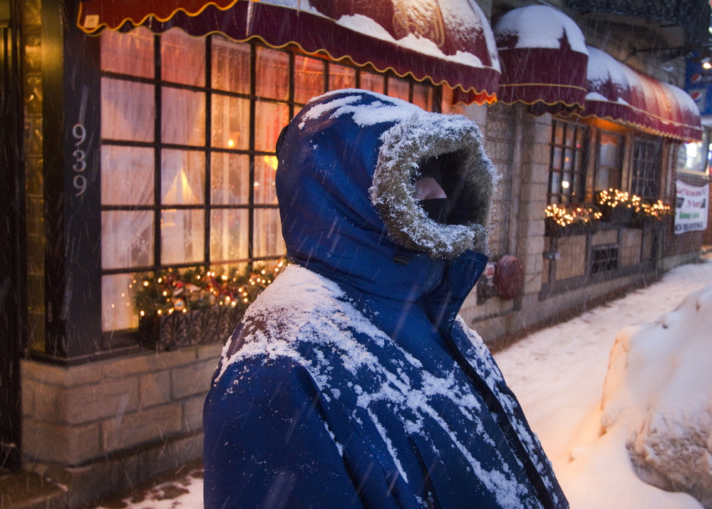 "Bundled in the appropriate gear, Darin Berrick of Portland stands in front of The Inn at St. John on Congress Street in Portland during heavy snowfall Tuesday evening. ""I wish it would go away. It's definitely getting old,"" said Berrick."