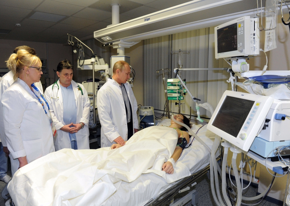 In this photo provided by RIA Novosti Kremlin, Russian President Vladimir Putin, center, speaks to skier Maria Komissarova in a hospital in Krasnaya Polyana, Russia, on Saturday, Feb. 15, 2014. The 23-year-old Russian ski cross racer fractured her spine during a training session Saturday and underwent a 6 hour surgery.