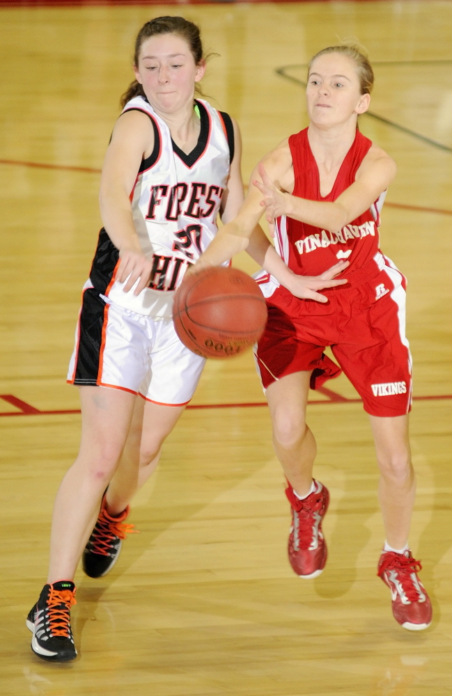 Forest Hills guard Keely Taylor, left, knocks the ball away from Vinalhaven's Hannah Noyes during a Western Class D girls' basketball quarterfinal Tuesday at the Augusta Civic Center. Top-seeded Forest Hills won, 70-27.