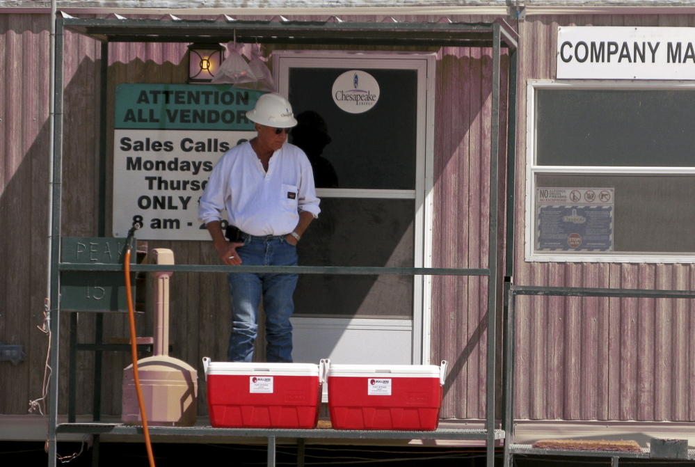 An oil worker takes a break at the Chesapeake Energy Corp., one of many companies tapping into the Eagle Ford shale in south Texas. In just a few years, the population of Carrizo Springs has gone from 5,600 to at least 40,000.