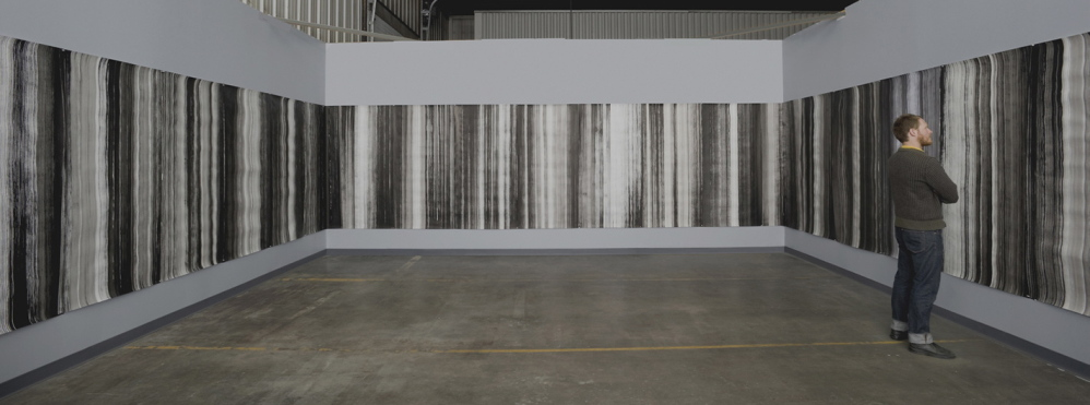 """Miles Anderson considers Larry Hayden's """"The Continuous Drawing"""" when the piece was hung in its entirety in the studio of photographer Tom McPherson. A portion will hang at Aucocisco Galleries beginning next week."""