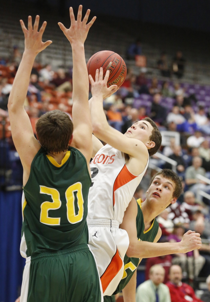 Derek Devereaux of Brunswick finds a room to get off a shot between Luke Davidson, left, and Dalton Rice of Oxford Hills during their Eastern Class A boys' basketball semifinal Wednesday at the Augusta Civic Center. Oxford Hills won in overtime, 61-58.