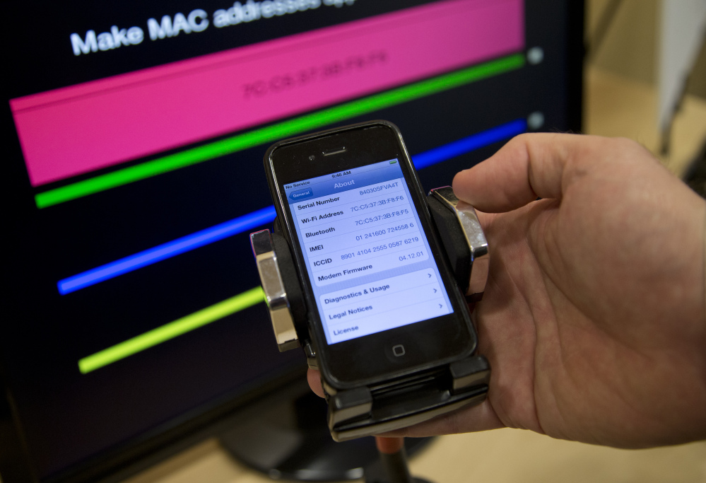 Technologist Seth Schoen holds a cellphone as it displays information, also seen on the screen behind, during a Federal Trade Commission mobile tracking demonstration Wednesday in Washington.
