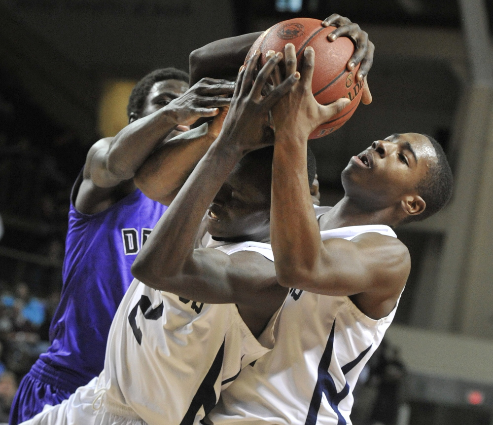 Portland's Jayvon Pitts-Young, right, battles teammate Stephen Alex and Deering's Patrick Lobor for a rebound Wednesday night during their Western Class A boys' basketball semifinal at the Cumberland County Civic Center. Portland kept its unbeaten record intact, winning 64-49.