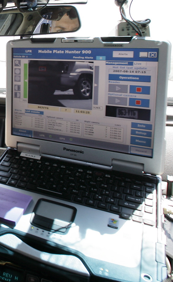 A dashboard computer in an Arizona police car reads and records license plates from passing cars.