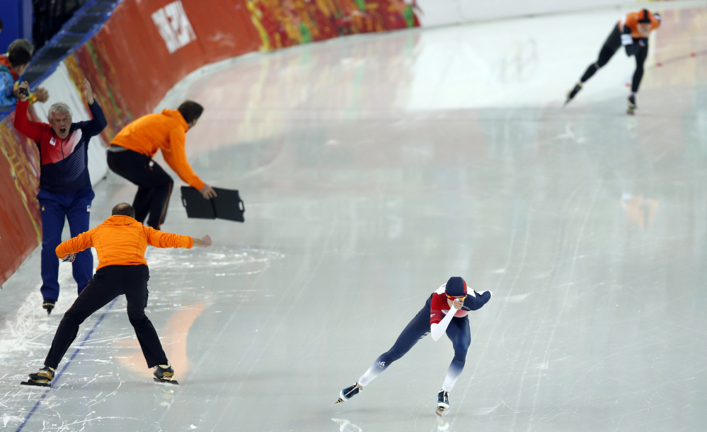 Coach Petr Novak of the Czech republic, left, screams as Martina Sablikova of the Czech Republic, front, skates against Ireen Wust of the Netherlands in the women's 5,000-meter speedskating race at the Adler Arena Skating Center during the 2014 Winter Olympics In Sochi, Russia, Wednesday, Feb. 19, 2014.