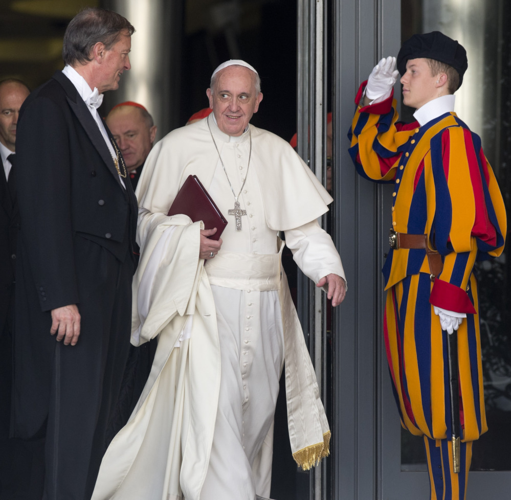 """Pope Francis leaves at the close of the morning session in the Synod hall at the Vatican City on Friday. He urges his cardinals to find ways to provide pastoral care that is 'intelligent, courageous and full of love"""" for divorced and remarried Catholics."""