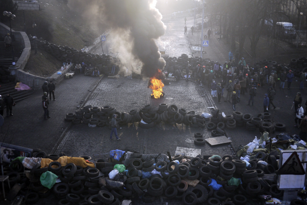 A fire burns at the barricades on the outskirts of Independence Square in Kiev, Ukraine, Friday. Ukraine's presidency said Friday that it has negotiated an international deal intended to end battles between police and protesters that have killed scores and injured hundreds.