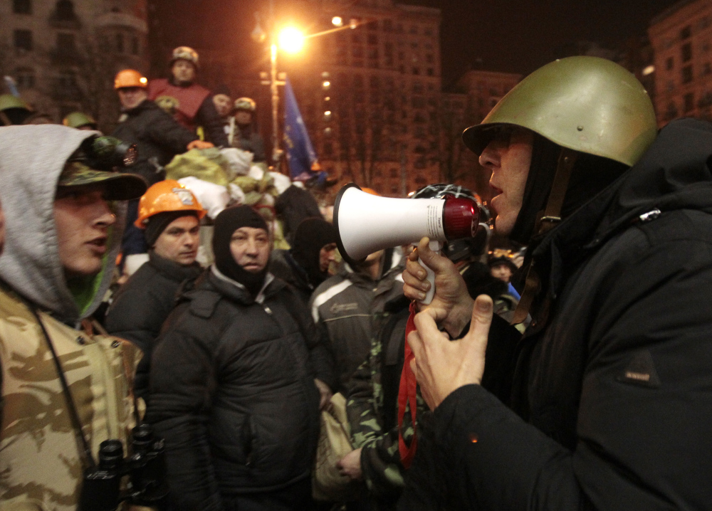 Opposition lawmaker Andriy Parubiy, right, tries to convince protesters to free a group of policemen, captured Thursday in Kiev. The policemen were eventually set free on Friday.