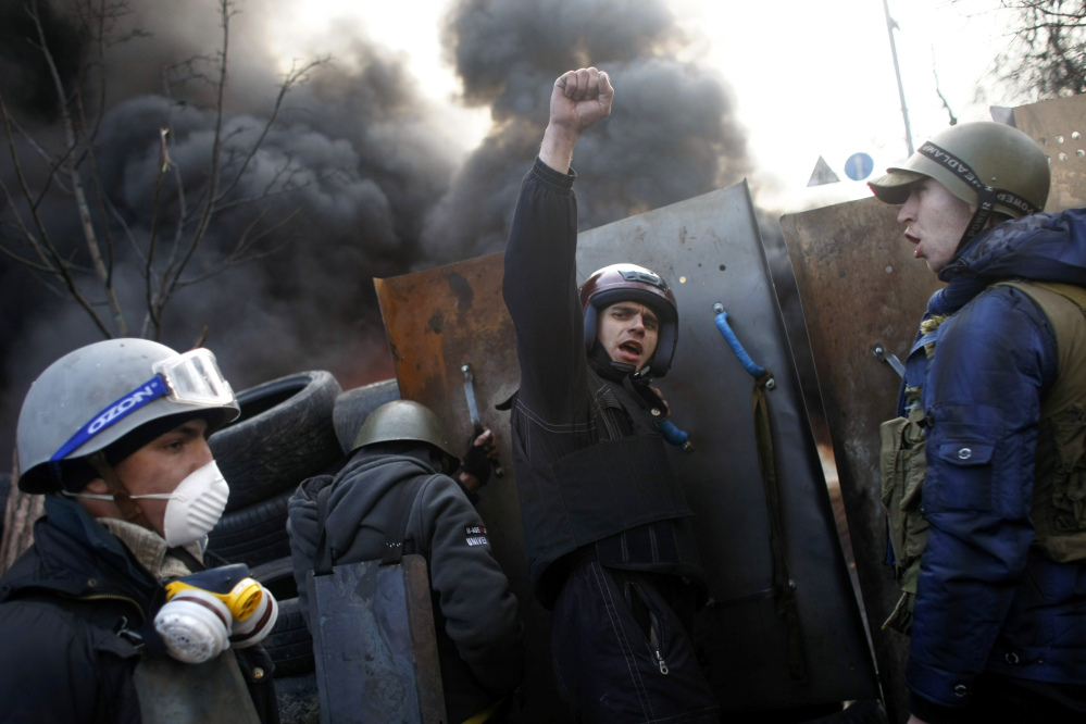 "Anti-government protesters shout ""Glory to the Ukraine"" as they man a barricade at Independence Square in Kiev on Friday."