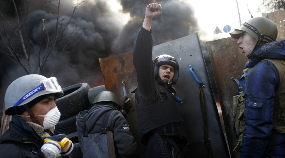 """Protesters shout """"Glory to the Ukraine"""" as they man a barricade at Independence Square in Kiev, Ukraine, on Friday."""