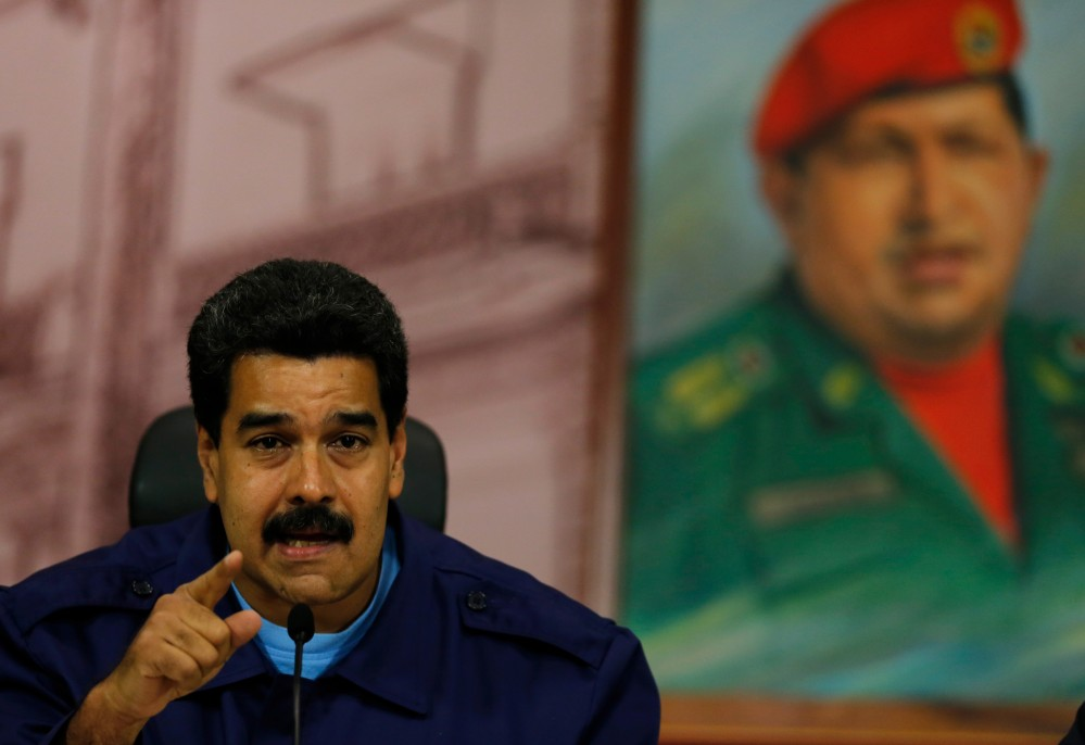 Venezuela's President Nicolas Maduro speaks next to a painting of the late Hugo Chavez during a news conference in Caracas on Friday. A report accuses the government of using excessive and unlawful force against protesters repeatedly since Feb. 12 and of censoring the news media.