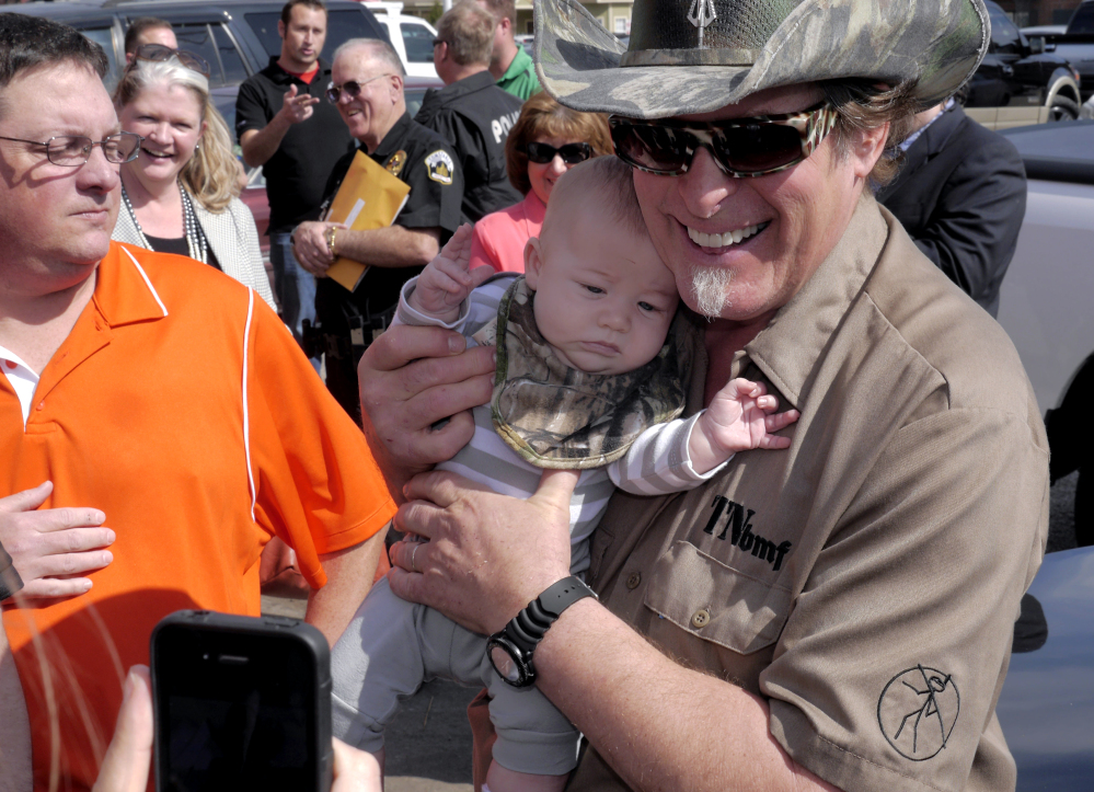 Three-month-old James Bodiford of Lavon, Texas, is photographed with rocker Ted Nugent as he visits with fans during a stop at a local restaurant Tuesday in Denton, Texas.