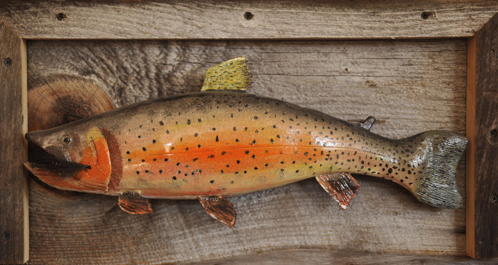 One of the pieces of art and memorabilia on the walls of Smith's office is a replica of a trout carved by his father.