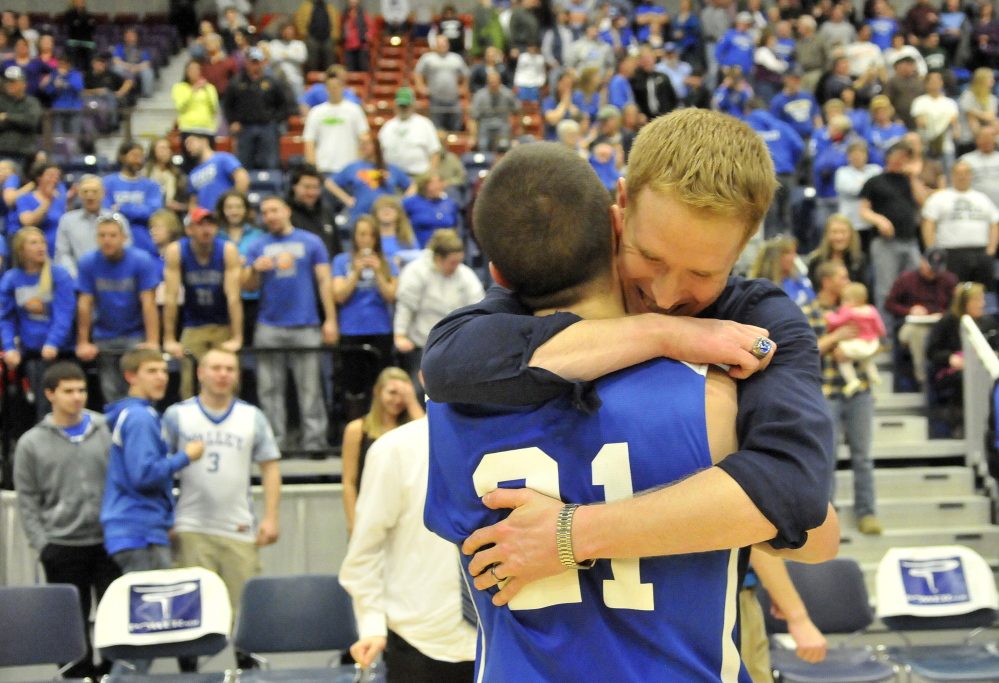 Valley assistant coach Jason Hartwell embraces Collin Miller after the Cavaliers rallied for a 50-49 win over Hyde in the Western Class D boys' basketball championship game Saturday at the Augusta Civic Center.