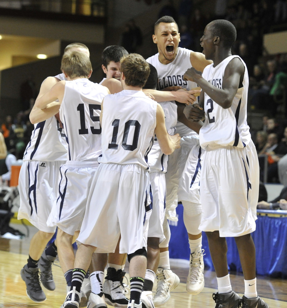 Portland players celebrate Saturday night after their 70-60 win over Bonny Eagle in the Western Class A boys' basketball championship game at the Cumberland County Civic Center. The Bulldogs will play for the state title next Saturday against reigning champion Hampden Academy in a matchup of unbeaten teams.