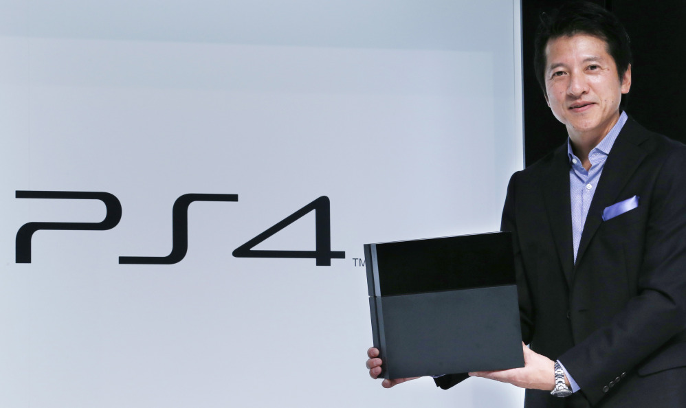 FILE - In this Monday, Sept. 9, 2013 file photo, Hiroshi Kawano, Sony Corp.'s chief of the game business in Japan and Asia, holds a PlayStation 4 during an event in Tokyo.