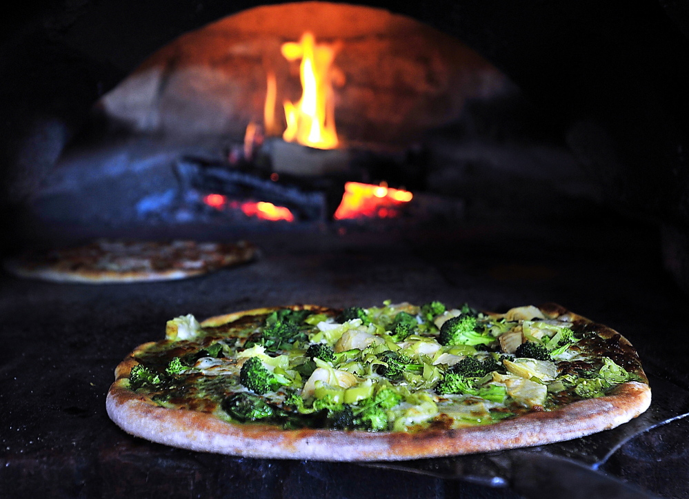 This Evergreenza pizza is ready to come out of the woodfired brick oven at Siano's Pizzeria. Ingredients include pesto, spinach artichokes, pepperoncinis & broccoli.