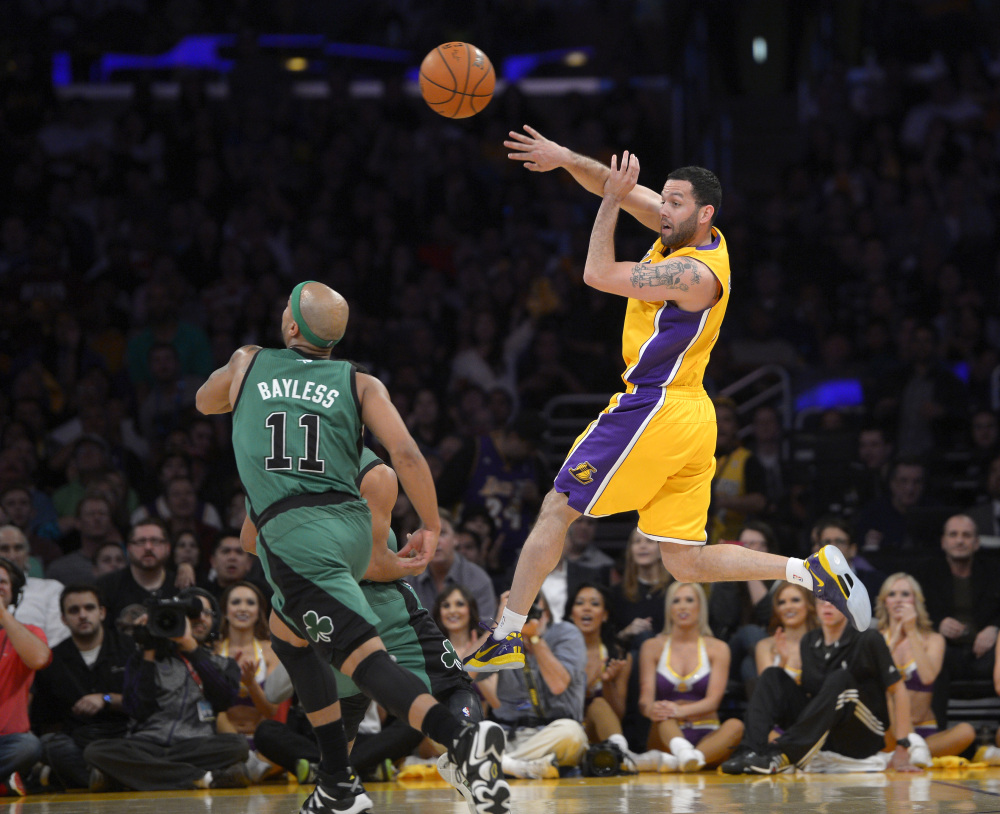 Los Angeles Lakers guard Jordan Farmar passes over Boston Celtics guard Jerryd Bayless in the second half Friday in Los Angeles.