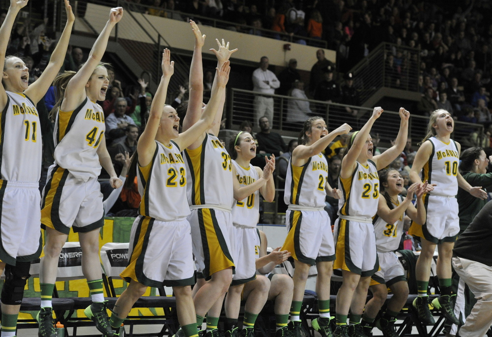 McAuley's players celebrate as their team wraps up a 50-25 win over Windham in the Western Class A girls' basketball championship game Saturday night at the Cumberland County Civic Center.
