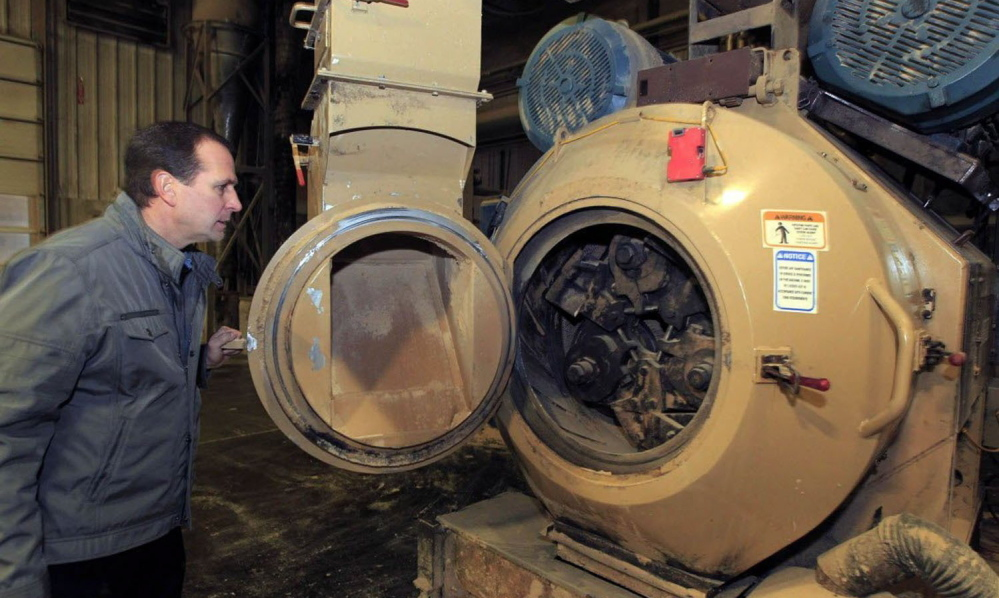 Larry Dejno shows a machine that grinds sawdust and wood shavings into pellets to be used in pellet stoves and furnaces at his Kenosha, Wis., plant. Dejno has seen an increase in sales of the pellets as prices rise on other home heating fuels.