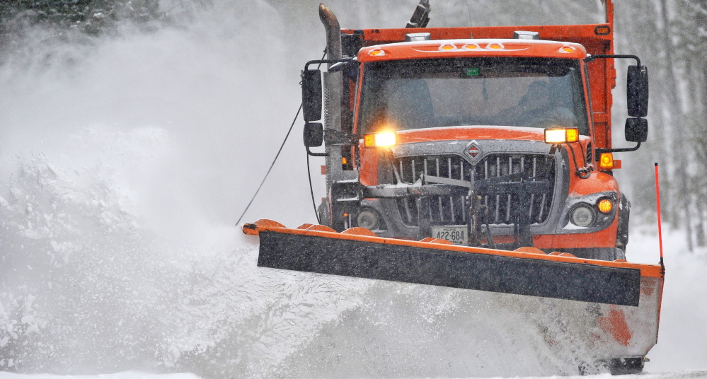 A city plow clears snow in Waterville during a recent storm. The increased use of salt brine to coat roads before a storm hits lets communities spread less salt and sand, cutting spending and runoff into lakes and streams.