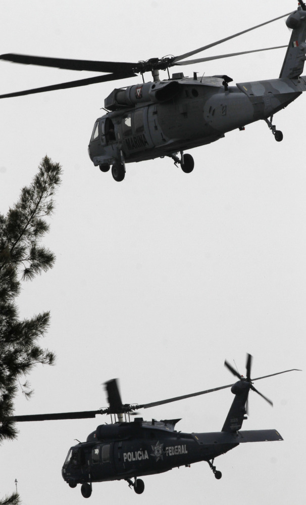 "A Mexican navy helicopter, top, escorts a federal police helicopter transporting Joaquin ""El Chapo"" Guzman after taking off from Mexico City on Saturday. Guzman arrived at the Mexico City airport after his arrest early Saturday and was taken directly to prison."