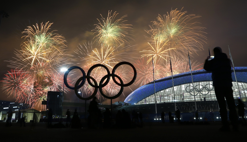 A man takes a photograph of fireworks during the closing ceremony of the 2014 Winter Olympics on Sunday.