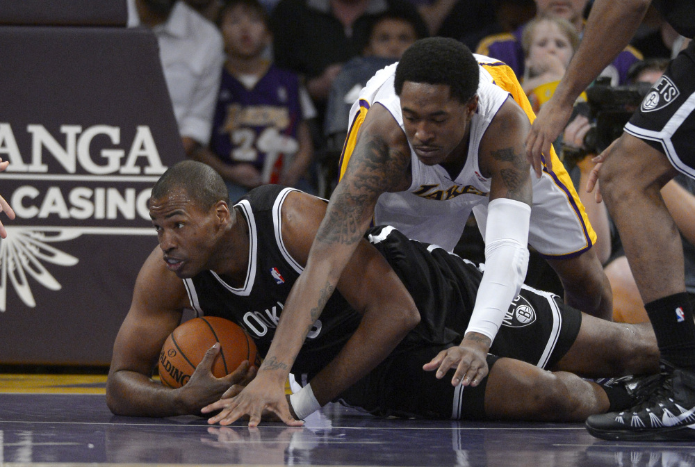 Brooklyn Nets center Jason Collins, left, battles for a loose ball with Los Angeles Lakers guard MarShon Brooks during the first half of an NBA basketball game Sunday in Los Angeles. Collins was making history by being the first openly gay NBA player on the court.