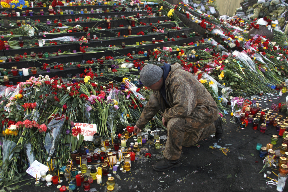 A man lights a candle at a memorial for the people killed in clashes with police at Independence Square in Kiev, Ukraine, Monday. Ukraine's acting government issued a warrant Monday for the arrest of President Viktor Yanukovych, accusing him of mass crimes against protesters who stood up for months against his rule.