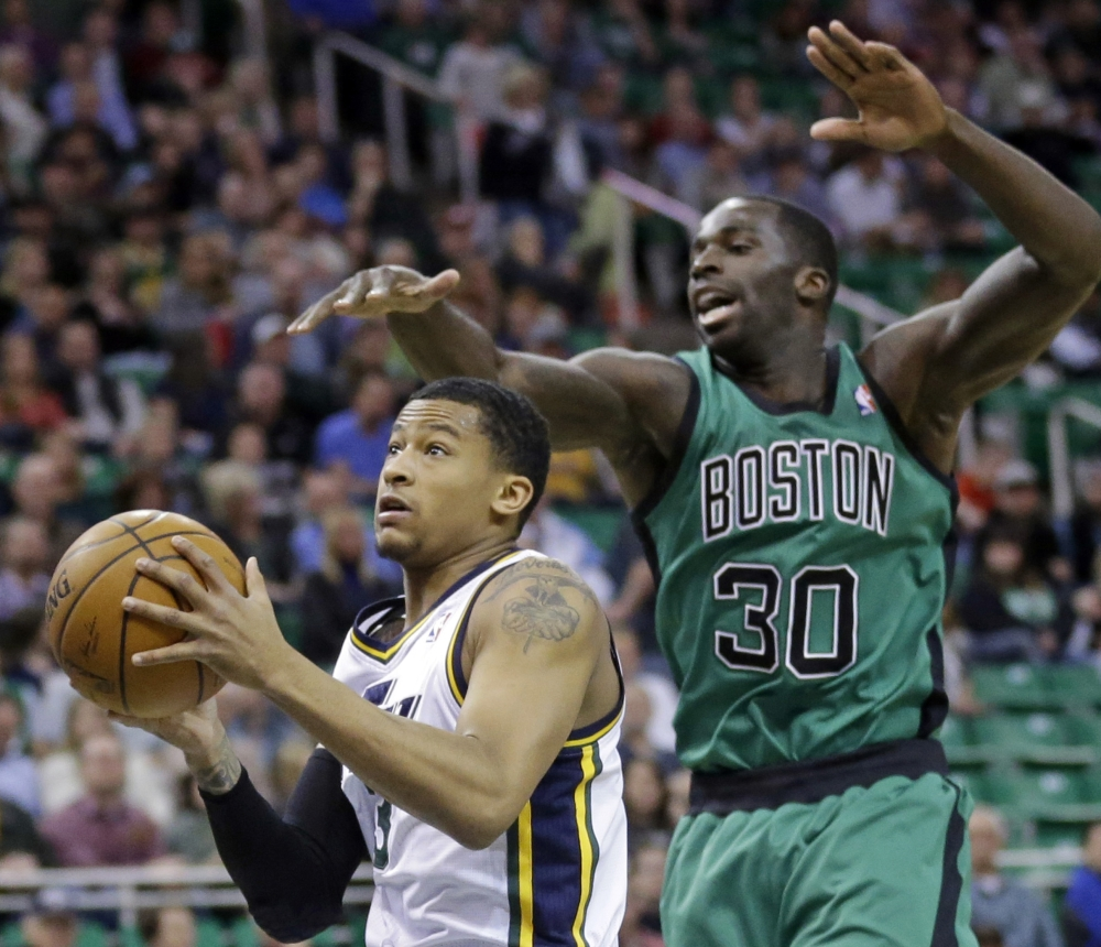 Utah's Trey Burke goes to the basket as Boston's Brandon Bass defends in the first quarter of a 110-98 win by the Jazz Monday night at Salt Lake City.