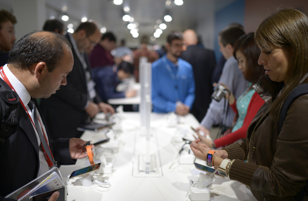 Visitors check the new devices of Samsung at the Mobile World Congress, the world's largest mobile phone trade show in Barcelona, Spain, Tuesday.