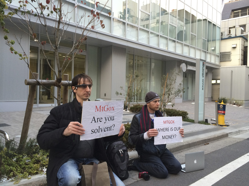 Bitcoin trader Kolin Burges, right, of London, and an American who would only give his first name, Aaron, hold protest signs as they conduct a sit-in in front of the office tower housing Mt. Gox in Tokyo on Tuesday. The website of major bitcoin exchange Mt. Gox went offline suddenly Tuesday. Burgess said he hopes to recoup $320,000 he has tied up with Mt. Gox.