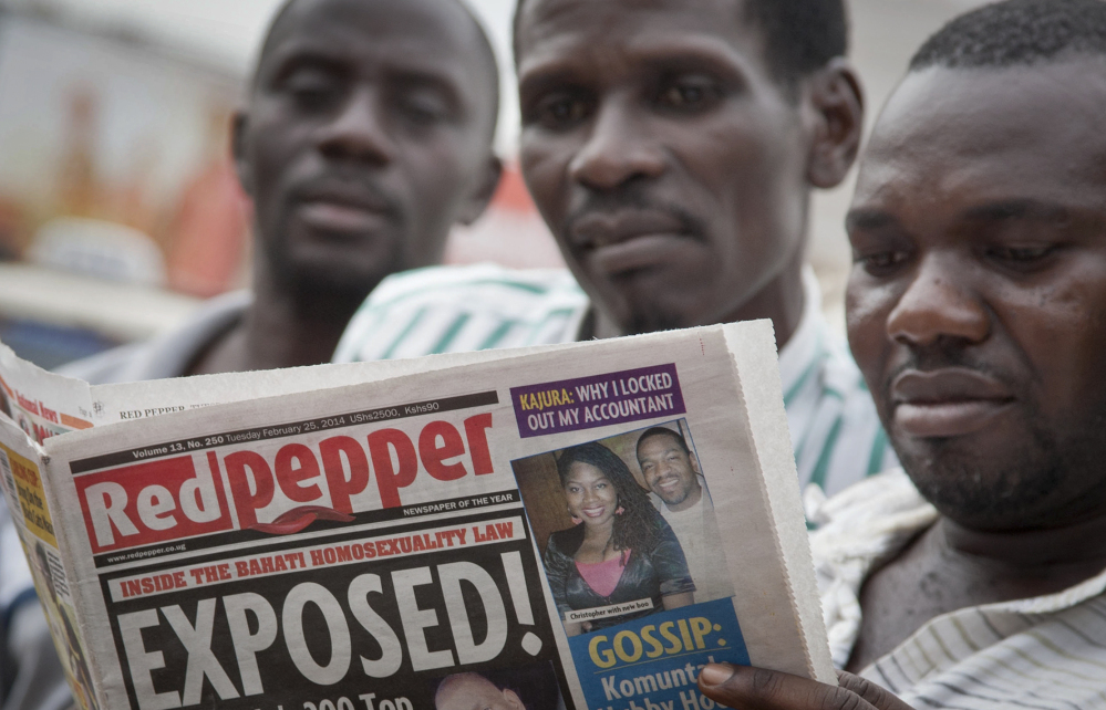 """A man reads the Red Pepper tabloid newspaper containing a list of what it calls the country's """"top 200"""" homosexuals, in Kampala, Uganda, on Tuesday."""