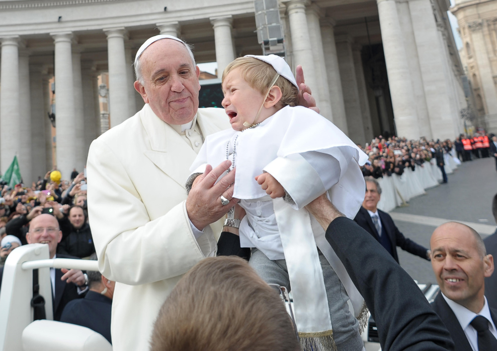 Nineteen-month-old Daniele De Sanctis, dressed up as a pope, is handed to Pope Francis as the pontiff is driven through the crowd during his weekly general audience in St. Peter's Square at the Vatican on Wednesday.