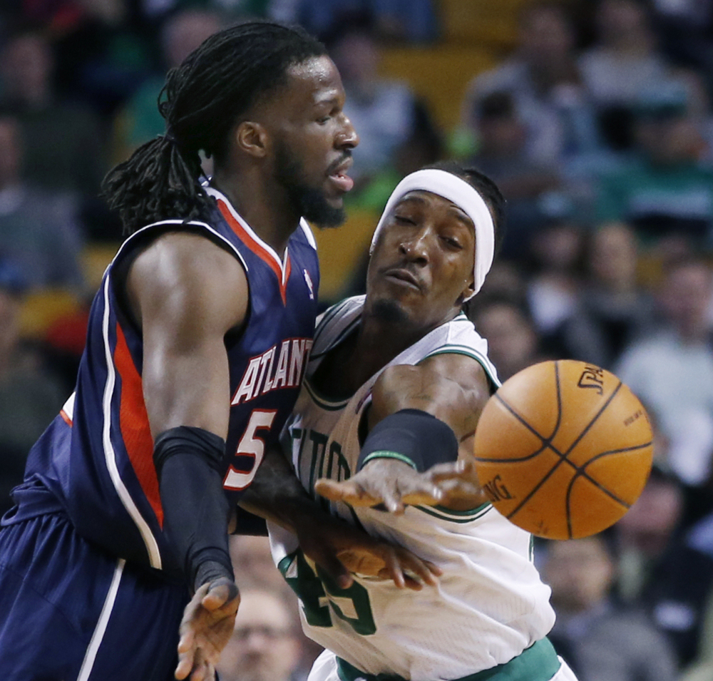 DeMarre Carroll of the Atlanta Hawks passes while being pressured by Gerald Wallace of the Boston Celtics during the first period of Boston's 115-104 victory Wednesday.
