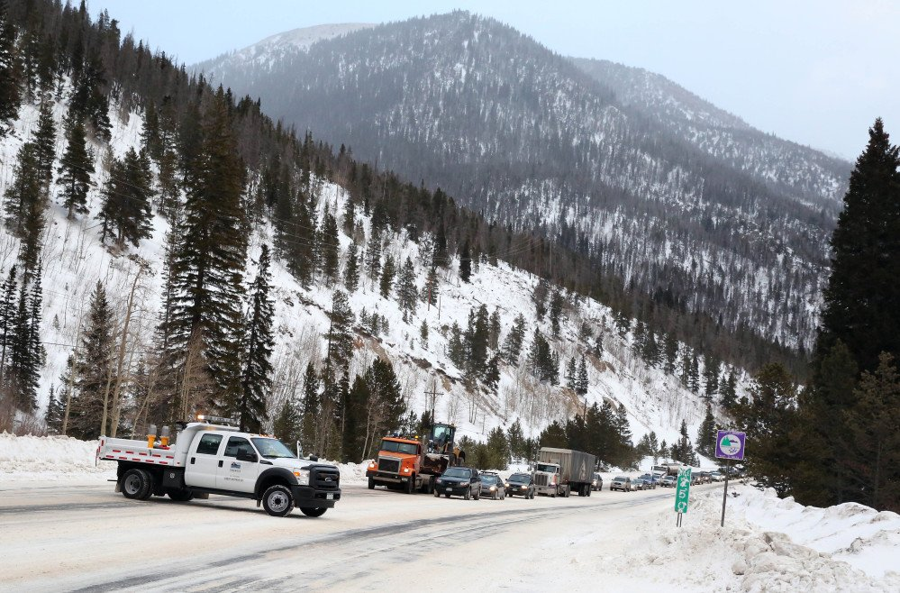 In this Feb. 21, 2014 photo, Colorado Department of Transportation employees stop traffic as they use an explosives launcher to try to trigger a controlled avalanche, near Empire, Colo. Lots of new snow and strong winds in the past month have fueled dangerous conditions from the Cascades to the Rockies, prompting forecasters to issue warnings of considerable or high avalanche dangers for many areas outside of established ski areas. (AP Photo/Brennan Linsley)