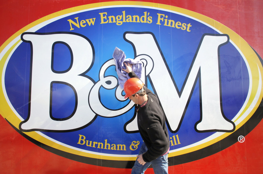 Gregory Rec/Staff Photographer Kyle Noyes, with Sign One of Falmouth, wipes down a new B&M sign before it gets lifted into place at the top of the bean factory in Portland in March 2010.