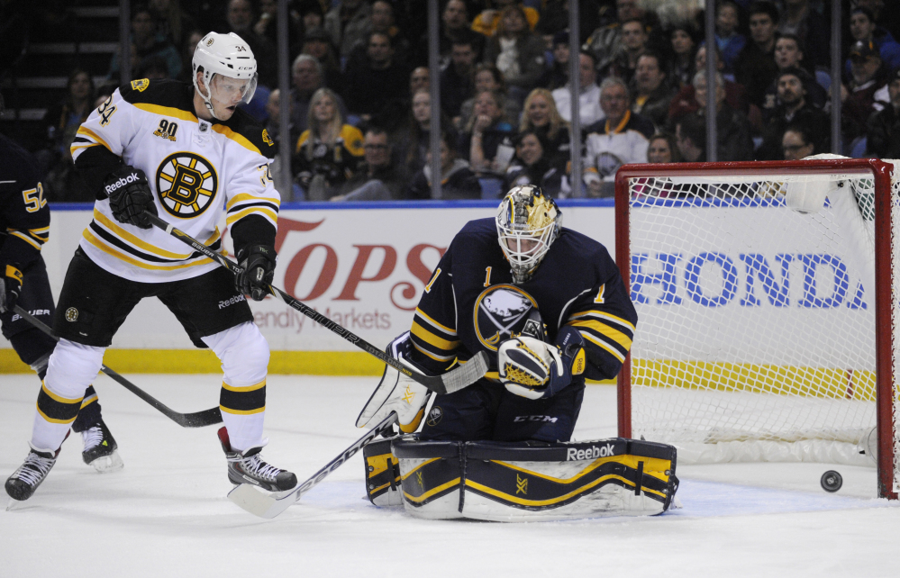 Carl Soderberg of the Boston Bruins deflects a shot just wide of the goal as Jhonas Enroth defends Wednesday night for the Buffalo Sabres, who won 5-4 in overtime at home.