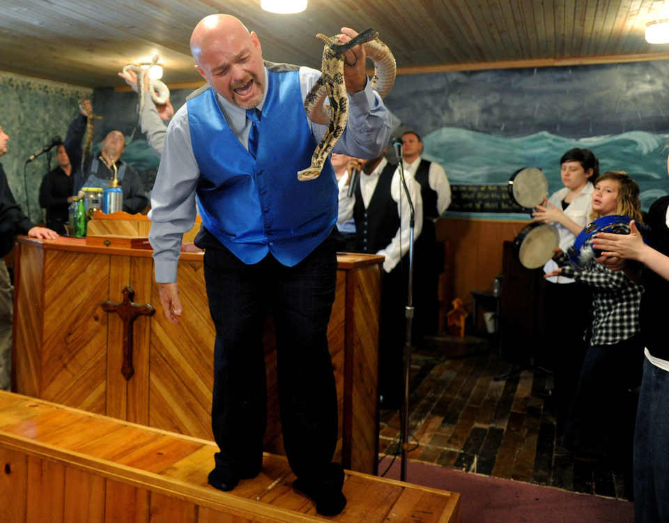 FILE - In this May 6, 2012 file photo, Jamie Coots, pastor of the Full Gospel Tabernacle in Jesus Name Church of Middlesboro, Ky, stands on a bench before the church, singing and holding a rattlesnake during service at Tabernacle Church of God in LaFollette, Tenn. on May 6, 2012.